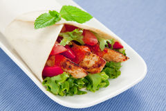 Chicken wrap. Healthy chicken tortilla wrap with lettuce, tomatoes, capsicum and  peri peri sauce Royalty Free Stock Photo