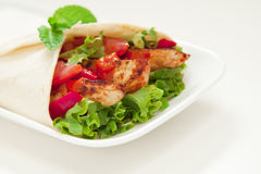 Chicken wrap. Healthy chicken tortilla wrap with lettuce, tomatoes, capsicum and  peri peri sauce Royalty Free Stock Photos