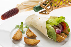 Chicken wrap with fresh vegetables and steak potatoes, on the pl. Ate decorated studio shot Royalty Free Stock Images