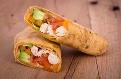 Chicken wrap sandwich. Chicken avocado wrap sandwich on table Stock Images