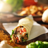Chicken wrap in tortilla with red peppers. Shot in square composition with lens flare in background Stock Image
