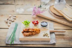 Chicken yakitori brochette. Chicken yakitori skewer with sauce,  red and green pepper on a wooden chopping table Royalty Free Stock Photo