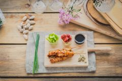 Chicken yakitori brochette. Chicken yakitori skewer with sauce,  red and green pepper on a wooden chopping table Royalty Free Stock Image