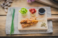 Chicken yakitori brochette. Chicken yakitori skewer with sauce,  red and green pepper on a wooden chopping table Royalty Free Stock Photography