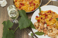 Chicken with zucchini. Zucchini stew with chicken,glass of wine and vine leaf Royalty Free Stock Photo