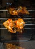 Chickens being grilled on metal spin in display. Chickens being grilled on metal spin in the view royalty free stock images