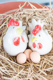 Chickens and eggs in straw nest. Ceramic chickens and eggs in straw nest Stock Photography