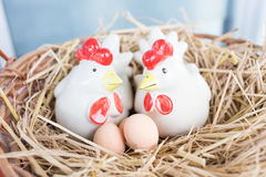 Chickens and eggs in straw nest Stock Photo