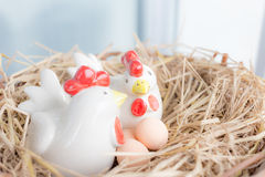 Chickens and eggs in straw nest Stock Image