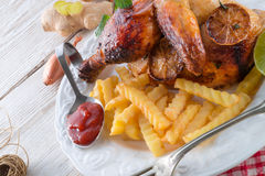 Chickens with French fries Stock Photos