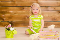 Chickens learning to read. Little blonde girl reading books and alive chickens on brown wooden wall background Stock Photos