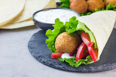 Chickpea falafel balls with vegetables and sauce, roll sandwich preparation, copy space Stock Photo
