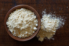 Chickpea flour in dark wooden bowl isolated on dark brown wood f. Rom above. Spilled flour stock image