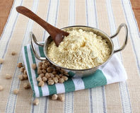 Chickpea Flour and Garbanzo Beans. Fresh, homemade chickpea flour, which is gluten-free, in a steel utensil with a wooden spoon, and garbanzo beans stock images