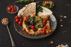 Hummus with vegetables and seafood on black background stock image