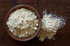 Chickpea mąka w ciemnym drewnianym pucharze odizolowywającym na ciemnego brązu drewnie f obraz stock
