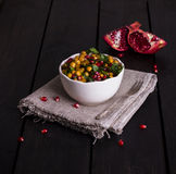 Chickpea Salad with Pomegranate. In a white bowl on a wooden table Royalty Free Stock Image