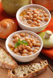 Chickpea soup. In white bowl on wooden table Royalty Free Stock Image