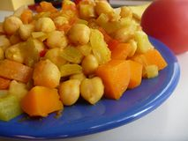 Chickpea vegetable salad on a blue plate Royalty Free Stock Photos