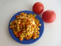 Chickpea vegetable salad on a blue plate Stock Photography