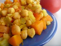 Chickpea vegetable salad on a blue plate Royalty Free Stock Images