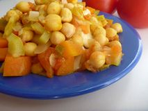 Chickpea vegetable salad on a blue plate Stock Photos