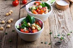 Chickpears和新鲜蔬菜沙拉在陶瓷碗 免版税库存图片
