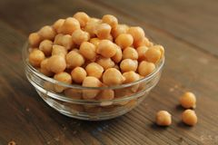 Chickpeas. In a clear bowl on a wooden table Royalty Free Stock Photo