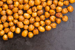 Chickpeas baked with spices closeup on black metal background with place for text Royalty Free Stock Photo