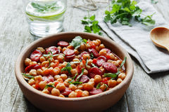 Chickpeas with chorizo in a clay bowl on the table close-up Stock Image