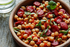 Chickpeas with chorizo in a clay bowl on the table close-up Stock Photos
