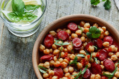 Chickpeas with chorizo in a clay bowl on the table close-up Stock Photography