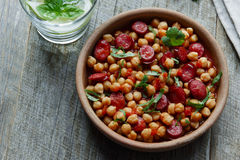 Chickpeas with chorizo in a clay bowl on the table close-up Royalty Free Stock Images
