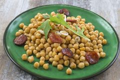 Chickpeas with chorizo on a green plate on wooden table Stock Photography