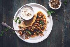 Chickpeas Crepe with Harissa Spicy Chicken, Kale, Cilantro and Yogurt Dukkah Sauce stock photos