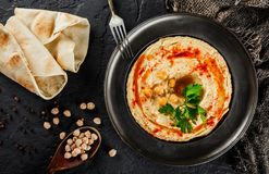 Chickpeas hummus with olive oil, paprika in a plate over dark stone background. Healthy vegan food, clean eating, dieting,. Top view stock photo