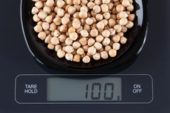 Chickpeas on kitchen scale Royalty Free Stock Image
