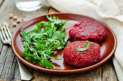 Chickpeas, quinoa and beet burgers with arugula. On a dark wood background. tinting. selective focus stock photography
