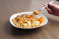 Chickpeas stew with a hand holding a spoon for eating. Royalty Free Stock Photo