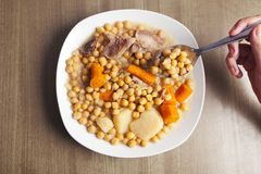 Chickpeas stew and hand with a spoon. Stock Photo