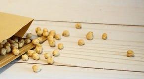 Chickpeas w papierowej torbie na drewnianym tle zamykają w górę Tak?e zna? jako garbanzo fasole zdjęcia stock