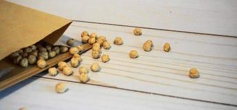 Chickpeas w papierowej torbie na drewnianym tle zamykają w górę Tak?e zna? jako garbanzo fasole zdjęcie stock
