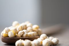 Chickpeas on a wood table. Some chickpeas on a wooed spoon in a wooden table stock photography