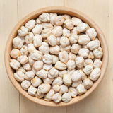 Chickpeas in wooden bowl, on wooden kitchen table Royalty Free Stock Photography