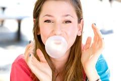 Chicle de globo de la chica joven que sopla Imágenes de archivo libres de regalías