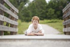 Chico del campo en un puente de madera Imagen de archivo