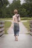 Chico del campo en un puente de madera Foto de archivo libre de regalías