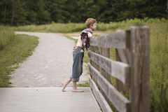 Chico del campo en una cerca de madera Imagen de archivo libre de regalías
