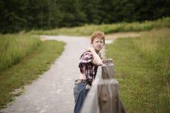 Chico del campo en una cerca de madera Imágenes de archivo libres de regalías