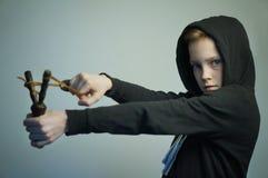 Chico malo adolescente con la catapulta y el corte de pelo elegante, tiro del estudio Foto de archivo